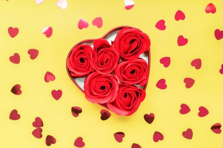 黄色背景上开着心形的红玫瑰。情人节的概念,浪漫的婚礼。复制空间