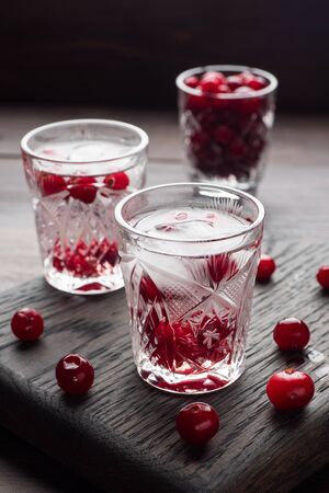 Stacks of vodka and cranberries on a wooden stand and background. Copy of the space. Bar alcoholic beverage tincture