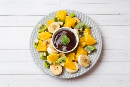Chocolate fondue with fruit on white table. concept summer party Copy space