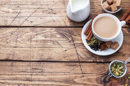 Indian drink masala tea with milk and spices. Cardamom sticks cinnamon star anise cane sugar Wooden background copy space. Zdjęcie Seryjne
