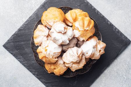 Profiteroles with custard and powdered sugar on a plate. Concrete grey table. Copy space.