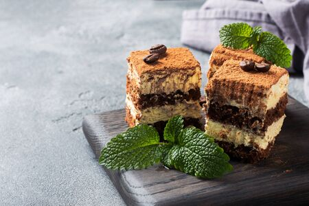 Pieces of tiramisu cake with delicate cream, coffee beans and mint leaves Dark concrete background with copy space.