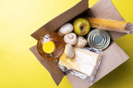 Food donation in a box on a yellow background. Copy of the space
