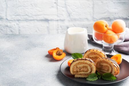 Pieces of sweet roll with cream filling on a plate. Fresh apricot berries and mint leaves.
