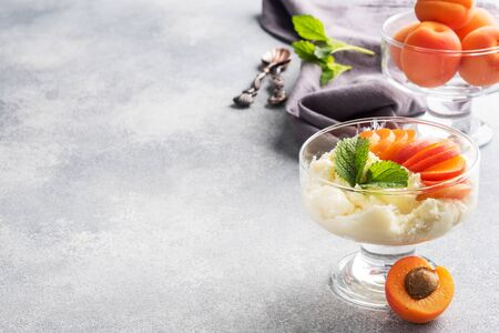 Dessert of sweet cottage cheese and fresh apricot berries with mint leaves. Imagens