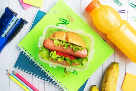 Hot dog with lettuce tomato and sausage. Notebooks and stationery. concept school Breakfast. Copy space.