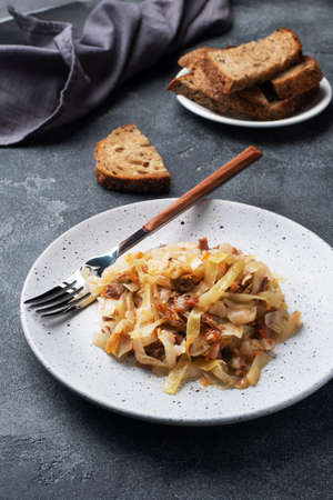 Stewed cabbage with meat on a plate. Dark concrete background