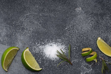 Slices of fresh lime, salt and rosemary dark concrete background. Copy space. Ingredients for making a tequila cocktail