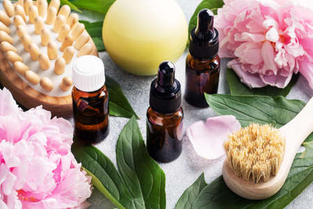 Concept SPA and Wellness. Massage brush, cosmetic oils and soap. Light background with peony flowers Foto de archivo