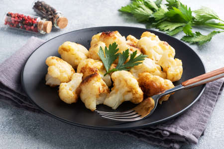 Fried cauliflower florets in batter on a black plate. Gray concrete background