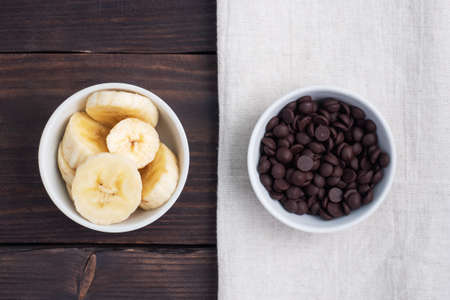Slices of sliced banana and chocolate drops in a plate Ingredients for dessert, concept
