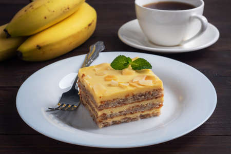 Banana sponge cake with nuts and mint. Delicious sweet dessert for tea, Dark wooden background 免版税图像