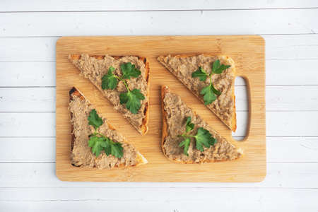 Sandwiches crispy toast and chicken liver pate with parsley leaves on a wooden cutting board. Copy space