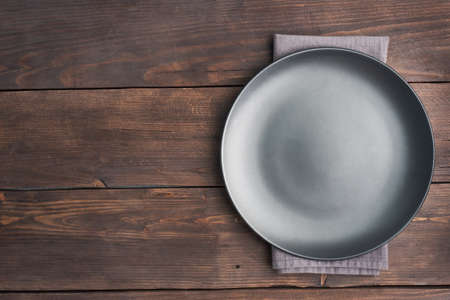 Empty black plate on wooden rustic background. Top view with copy space