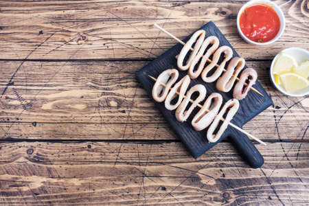 Fried squid rings on a skewer with tomato sauce and lemon. Dark wooden background copy space. Top view 免版税图像