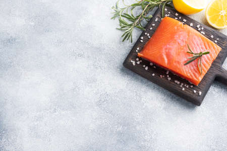 Salmon fillet, red salted fish on a wooden chopping Board. Lemon, rosemary spices Copy space.