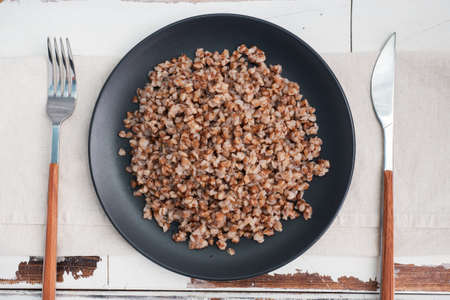 Boiled buckwheat on a plate. Healthy porridge enriched with vitamins copy space, top view. 免版税图像