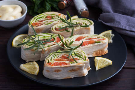 Rolls of thin pita bread and red salted salmon with lettuce leaves on a black ceramic plate, dark wooden background