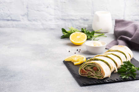 Rolls of thin pita bread and red salted salmon with lettuce leaves On a slate stand, gray concrete background. Copy space