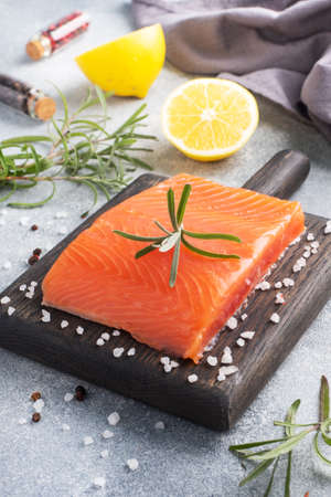 Salmon fillet, red salted fish on a wooden chopping Board. Lemon, rosemary spices 免版税图像