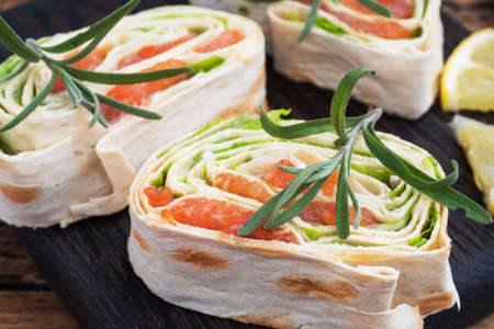 Rolls of thin pita bread and red salted salmon with lettuce leaves on a wooden cutting Board