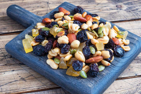 A mixture of nuts and dried fruits on a wooden chopping board, rustic background. Concept of healthy food