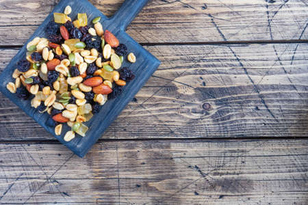 A mixture of nuts and dried fruits on a wooden chopping board, rustic background. Concept of healthy food Copy space
