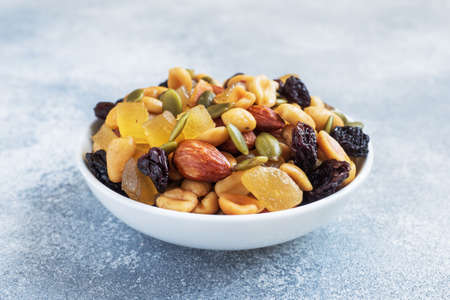 A mixture of nuts and dried fruits in a ceramic plate on a gray concrete background. Concept of healthy food 免版税图像