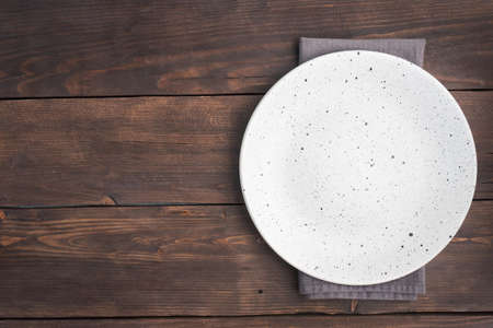 Empty white plate on wooden rustic background. Top view with copy space