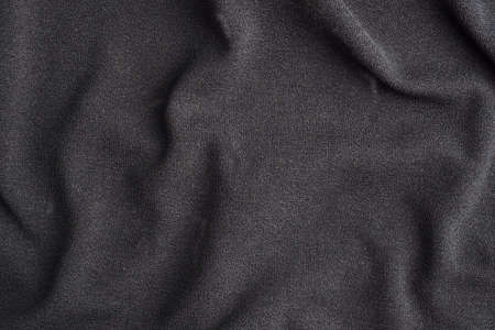 Background is made of black textile material, the texture of a piece of clothing