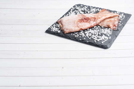 Raw squid carcass with spices and coarse salt on a black slate board. copy space Top view