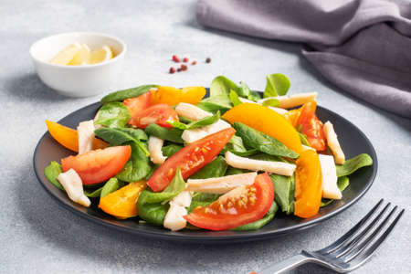Salad of boiled squid, fresh tomatoes, spinach leaves. Delicious bright diet dish with vegetables and seafood