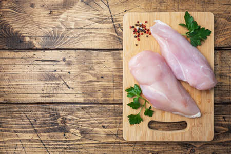 Raw chicken breast fillet on a wooden chopping board. Wooden rustic background top view, copy space