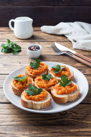 Sandwiches with bread zucchini caviar tomatoes onions. Homemade vegetarian food. Canned stewed vegetable wooden background