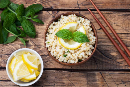 Boiled bulgur with fresh lemon and mint on a plate. A traditional oriental dish called Tabouleh wooden background rustic top view, copy space