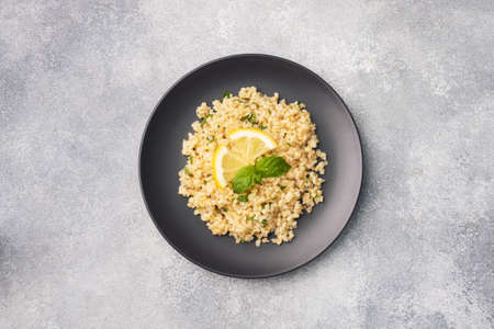Boiled bulgur with fresh lemon and mint on a plate. A traditional oriental dish called Tabouleh Gray concrete background top view, copy space