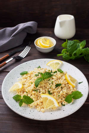 Boiled bulgur with fresh lemon and mint on a plate. A traditional oriental dish called Tabouleh dark wooden background. 免版税图像