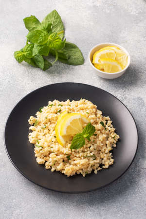 Boiled bulgur with fresh lemon and mint on a plate. A traditional oriental dish called Tabouleh Gray concrete background
