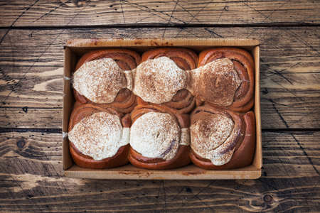 Kanelbulle Cinnamon buns with buttercream on a rustic wooden table. Homemade fresh pastries top view, copy space.