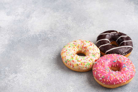 Assortment of donuts in icing on a gray concrete table, copy space