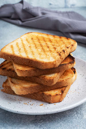 Bread toast crispy for sandwiches on a plate on a gray concrete table 免版税图像