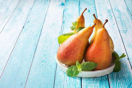 Fresh juicy Pears Conference on blue wooden bright background. Autumn harvest of ripe fruit copy space