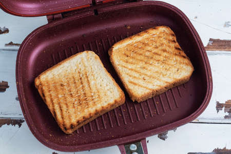 Two pieces of toasted bread in a grill pan. Close up 免版税图像
