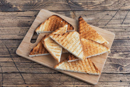 Slices of crispy bread toast for sandwiches on a cutting board, wooden rustic background. copy space 免版税图像