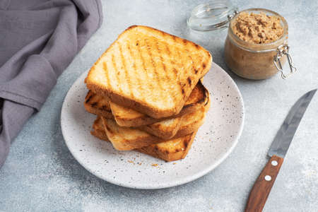 Bread toast crispy for sandwiches on a plate on a gray concrete table A jar of chicken pate.