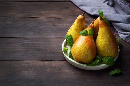 Fresh juicy Pears Conference on dark wooden rustic background. Autumn harvest of ripe fruit copy space