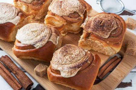 Kanelbulle Cinnamon buns with buttercream on a rustic wooden table. Homemade fresh pastries