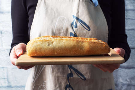 A fresh baguette of bread on a wooden board is held in the hands of a female chef