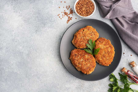 Buckwheat cutlets with cheese and parsley on a plate Healthy diet food copy space, top view. 免版税图像