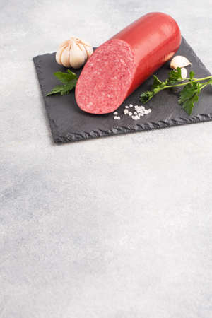 A loaf of salami Servelat sausage on a cutting Board with parsley and spices and garlic top view copy space